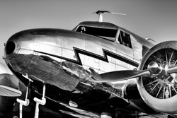 Low, front-quarter view of a gleaming, silver, vintage, lockheed electra from the golden age of aviation.
