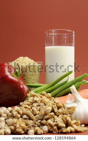 Low GI Foods - milk, brown rice, oatmeal, red capsicum pepper, green beans, garlic, raw carrot, walnuts, chickpeas, wholemeal pasta and buckwheat noodles. Vertical with copy space.