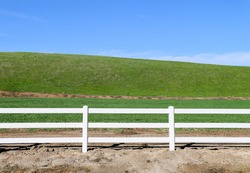 low grassland hillside hills pasture with bright sunny blue sky and wooden white picket farm livestock fence