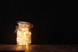low key and vintage filtered image of fairy lights in mason jar with. selective focus