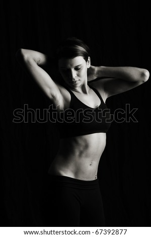 Low key Artistic photo of attractive woman dancing. In studio on black