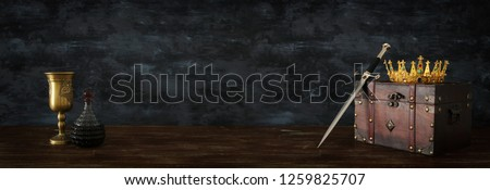 low key banner of beautiful queen/king crown, wine cup and sword. fantasy medieval period #1259825707