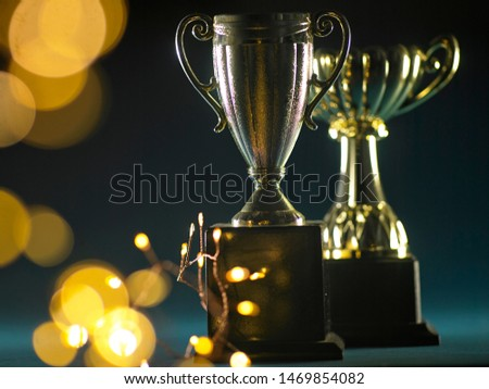 Low key group golden trophies on the blur blue background with abstract shiny lights