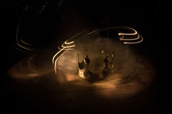 low key image of beautiful crown over wooden table. vintage filtered. fantasy medieval period. Selective focus. Colorful backlight