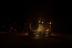 low key image of beautiful kings crown over wooden table. vintage filtered. fantasy medieval period. Selective focus. Colorful backlight