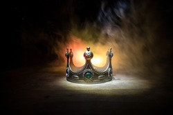 low key image of beautiful queen crown over wooden table. vintage filtered. fantasy medieval period. Selective focus. Colorful backlight