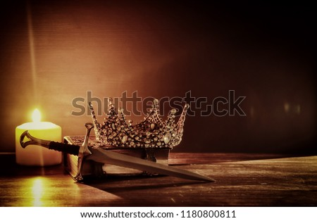 low key image of beautiful queen/king crown and sword. fantasy medieval period. Selective focus