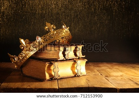 low key image of beautiful queen/king crown on old books. vintage filtered. fantasy medieval period