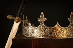 low key image of beautiful queen/king crown over antique box next to sword. fantasy medieval period. Selective focus