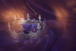 low key image of beautiful queen/king crown over dark royal purple delicate silk. fantasy medieval period