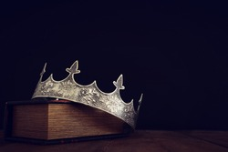 low key image of beautiful queen/king crown over old book and wooden table. vintage filtered. fantasy medieval period