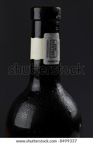 low-key image of dark wine bottle covered with condensation, against dark ground; background easily extendable to increase copy space