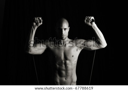 Low key image of fitness man working out with resistance bands
