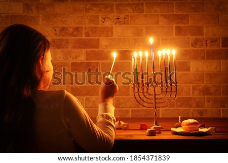 Low key image of jewish holiday Hanukkah background with girl looking at menorah (traditional candelabra) and burning candles Сток-фото ©