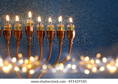 Low key Image of jewish holiday Hanukkah background with menorah (traditional candelabra) and burning candles and glitter overlay