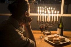Low key Image of jewish holiday Hanukkah (holiday of lights) with menorah, burning candles, donuts and wine. View to the night Tel Aviv from window
