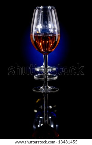Low key image of three wine glasses, filled with red liquid on a reflective surface with a blue separation light.
