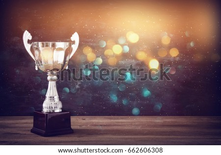 low key image of trophy over wooden table and dark background, with abstract glitter lights #662606308