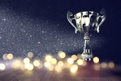 low key image of trophy over wooden table and dark background, with abstract shiny lights
