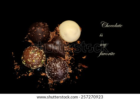 Low Key lighting on Chocolates sitting on a reflective black background and space for your text - Chocolates are my favorite