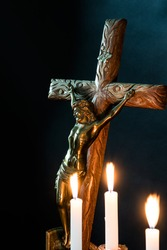 Low key of antique crafted crucifixion on crafted wooden cross with blurry lit candles foreground