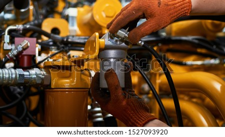 Low key photo of hydraulic pipes maintenance on heavy industry machine in a garage. Photo stock ©