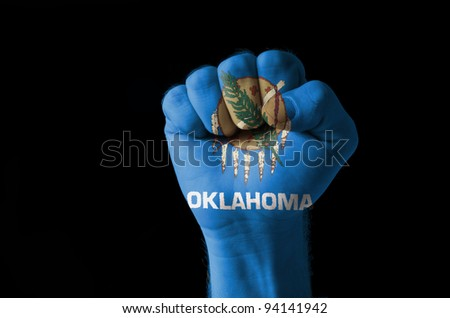 Low key picture of a fist painted in colors of american state flag of oklahoma