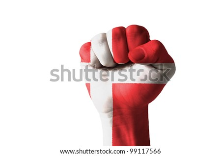 Low key picture of a fist painted in colors of denmark flag