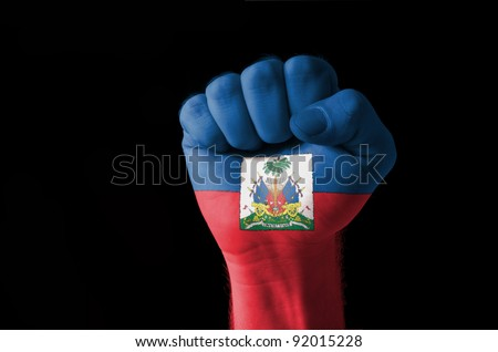 Low key picture of a fist painted in colors of haiti flag