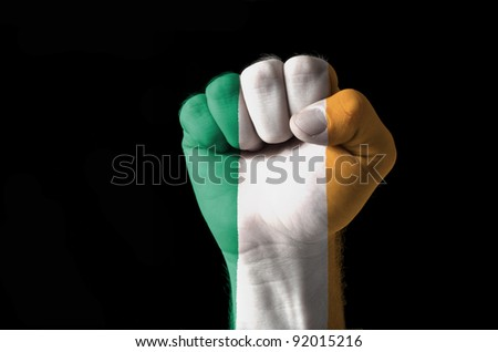 Low key picture of a fist painted in colors of ireland flag