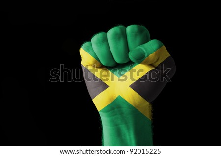 Low key picture of a fist painted in colors of jamaica flag