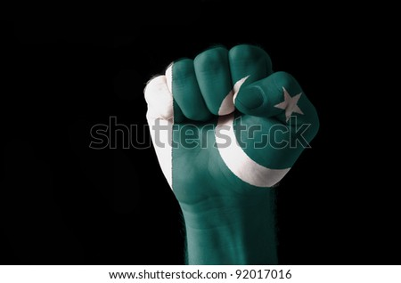 Low key picture of a fist painted in colors of pakistan flag