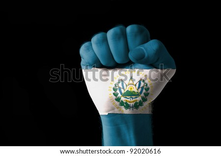 Low key picture of a fist painted in colors of san salvador flag