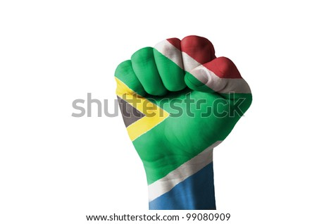 Low key picture of a fist painted in colors of south africa flag