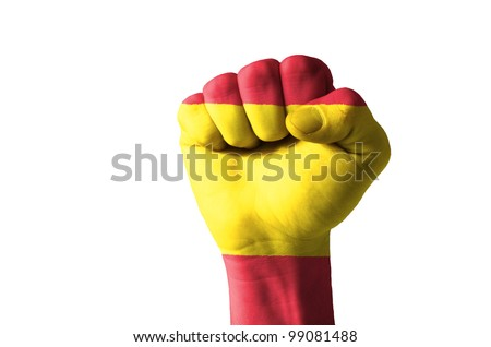 Low key picture of a fist painted in colors of spain flag