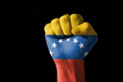 Low key picture of a fist painted in colors of venezuela flag