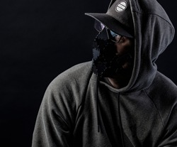 Low key portait of a man wearing a hoodie and a black face mask