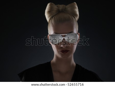 Low key portrait of a beautiful woman in stylish glasses