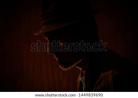 low key portrait of a man with a borsalino type hat, mysterious atmosphere, he could be an investigator, the man is serious and looks down Stock photo ©