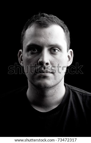 Low key portrait of a serious man in his late twenties in black and white.  Shallow depth of field.