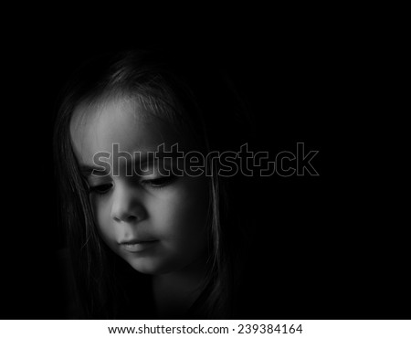 Low key Portrait of a young child. Sad looking girl is looking down.Picture is black and white.