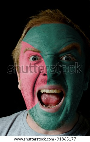 Low key portrait of an angry man whose face is painted in colors of bangladesh flag