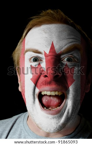 Low key portrait of an angry man whose face is painted in colors of canadian flag