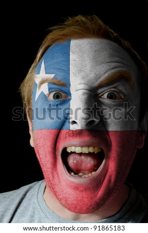Low key portrait of an angry man whose face is painted in colors of Chile flag