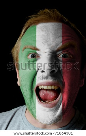 Low key portrait of an angry man whose face is painted in colors of italian flag