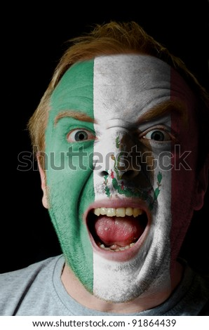 Low key portrait of an angry man whose face is painted in colors of mexico flag