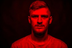 Low key portrait of bearded young man full-face looking at camera in red light on black backdrop. Victim of war, terror, social inequality concept