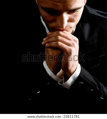 Low-key portrait of businessman praying for success
