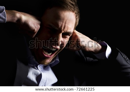 Low-key portrait of desperate businessman in dark suit screaming and holding both fists at head expressing strong despair, isolated on black background.
