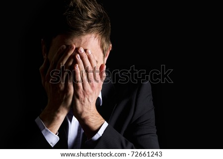 Low-key portrait of desperate office manager in dark suit covering his face with both hands, isolated on black background with copy-space.